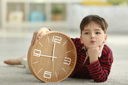 Cute little boy with big clock sitting on floor at home Banque d'images