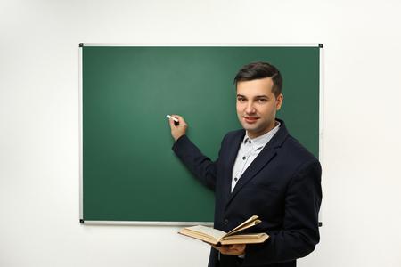 Handsome young teacher near blackboard in classroom Фото со стока