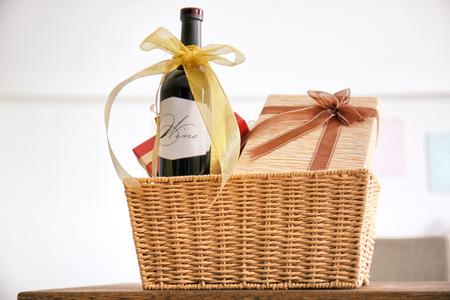 Wine bottle with gift boxes in wicker basket on light background