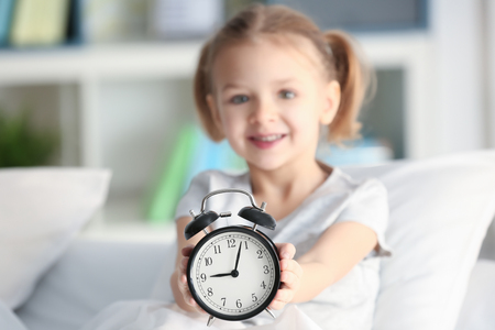 Cute little girl with alarm clock in bed Stockfoto