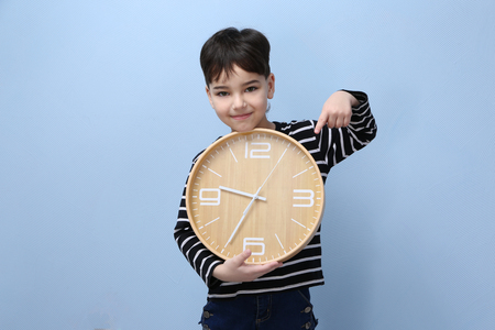 Cute little boy with big clock on color background Banque d'images