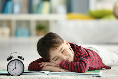 Cute little boy with book and alarm clock sleeping on floor at home