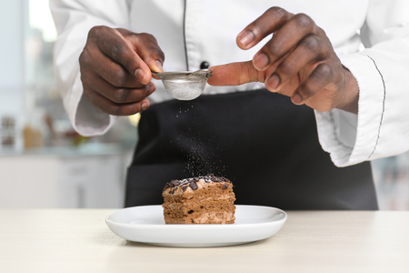 African American chef sifting sugar on tasty cake in kitchen, closeup