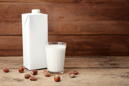 Carton box and glass of milk on wooden background 版權商用圖片