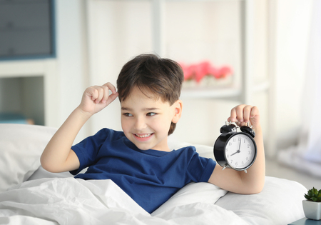 Cute little boy with alarm clock in bed