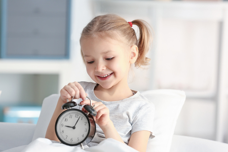 Cute little girl with alarm clock in bed Reklamní fotografie