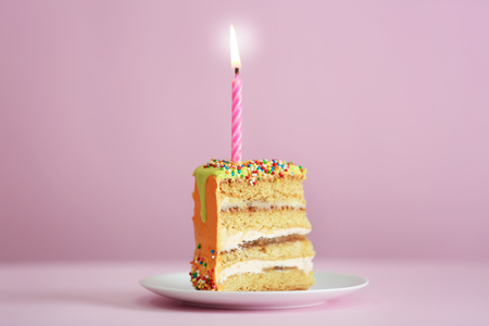 Slice of birthday cake with candle on color background Banque d'images
