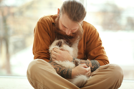 Young bearded man with fluffy cat sitting on floor
