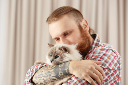 Young bearded man holding fluffy cat on blurred background Archivio Fotografico
