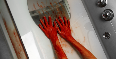 Bloody hands of depressed woman on mirror in shower