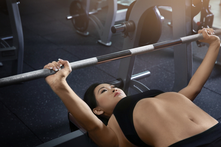 Young sporty woman training with barbell at gym Stock Photo
