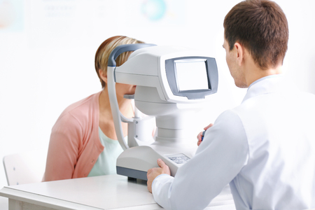 Ophthalmologist measuring intraocular pressure of woman in clinic