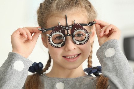 Cute little girl with trial frame in ophthalmologists office Stockfoto