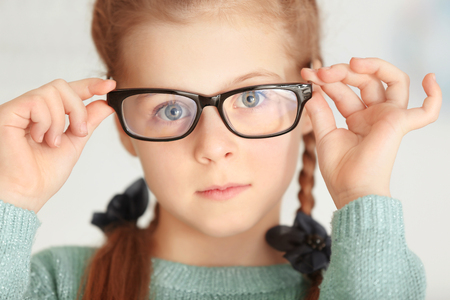 Cute little girl with glasses on blurred background, closeup