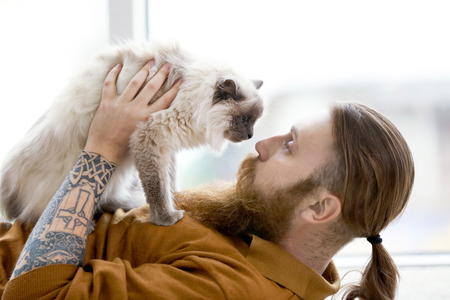 Young bearded man with fluffy cat lying on floor
