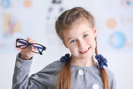 Cute little girl with glasses in ophthalmologists office