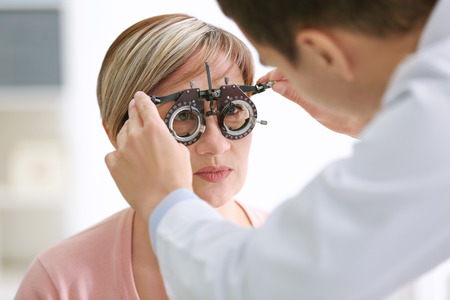 Ophthalmologist examining eyes of mature woman in clinic, closeup Stockfoto