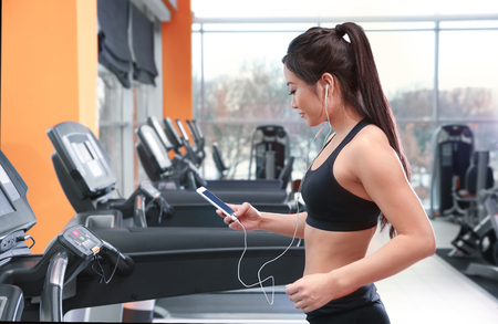 Sporty woman running on treadmill at gym