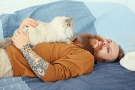 Young bearded man with fluffy cat lying on bed Archivio Fotografico