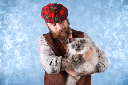 Young bearded man in plaid cap with fluffy cat on light background
