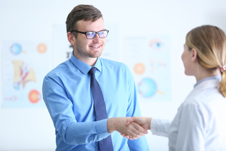 Patient shaking hands with doctor in medical office Standard-Bild