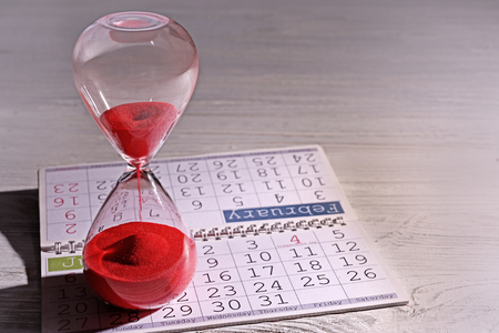 Time passing concept. Crystal hourglass with red sand and calendar on light wooden background 스톡 콘텐츠