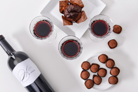 Delicious chocolate cake, truffles and red wine on white background Archivio Fotografico