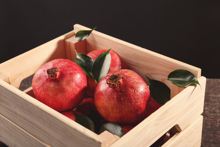 Wooden box with pomegranates on gray table