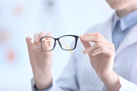 Doctor manos sosteniendo vasos sobre fondo borroso