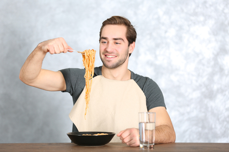 Handsome man eating pasta on table against light background 免版税图像