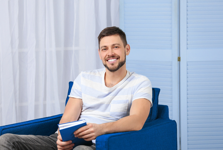 Handsome young man reading book while sitting in arm-chair at home