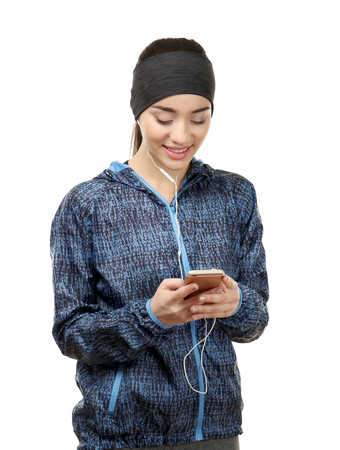 Young woman in sportswear with mobile phone on white background Standard-Bild