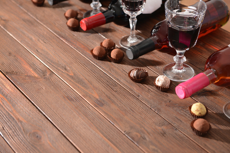 Wine and chocolates on wooden background