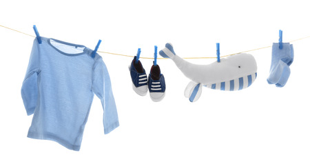 Clothesline with hanging baby clothes on white background