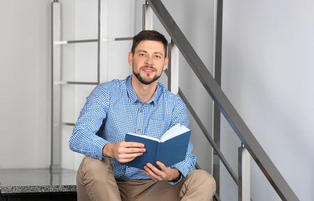 Handsome young man reading book while sitting on stairs at home Foto de archivo
