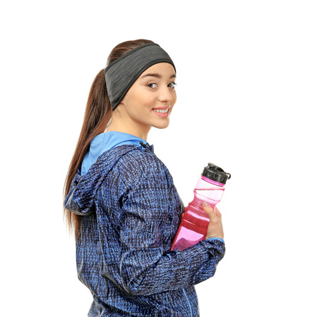 Young woman in sportswear with bottle on white background