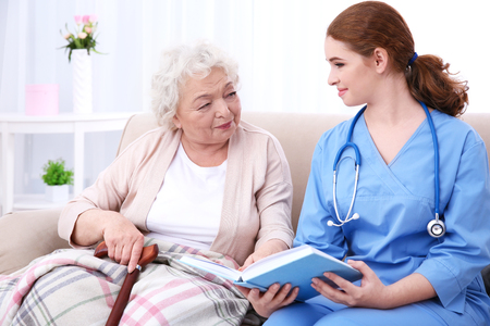 Nurse reading book to elderly woman on couch