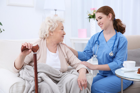 Nurse talking with elderly woman in light room Imagens