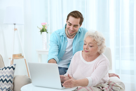 Young man caring about grandmother at home