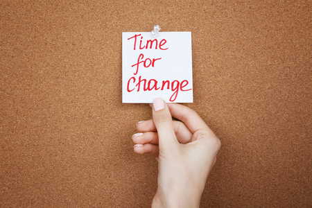 Female hand holding note with phrase TIME FOR CHANGE on cork board background
