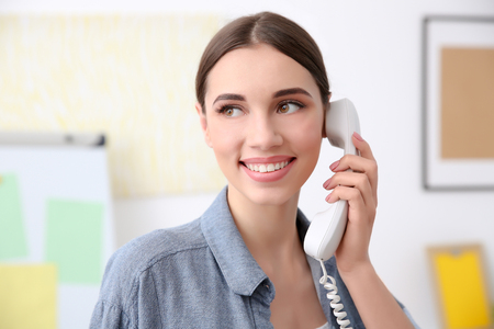 Beautiful young woman talking by telephone in office Foto de archivo