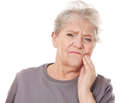 Elderly woman suffering from toothache on white background 写真素材