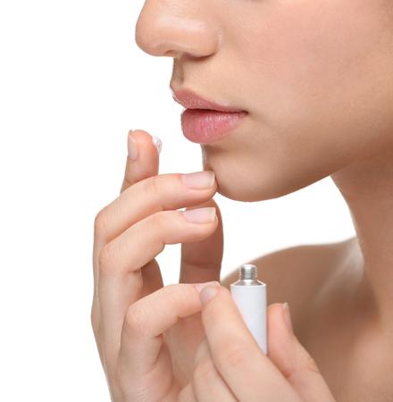 Woman applying cream onto lips on white background