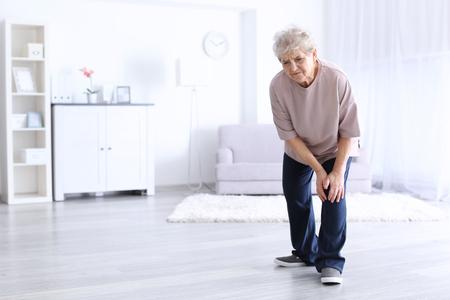 Anciana que sufre de dolor en la rodilla en casa