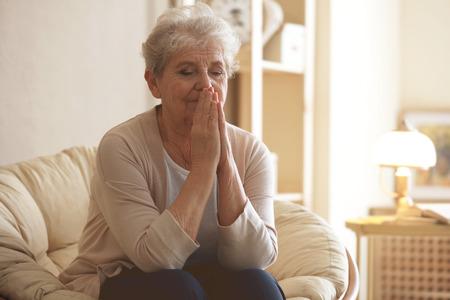 Betende ältere Frau, die zu Hause auf der Lounge sitzt