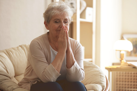 Praying elderly woman sitting on lounge at home