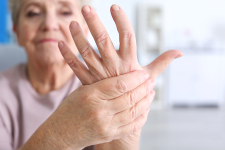Oudere vrouw die lijdt aan pijn in de hand, close-up