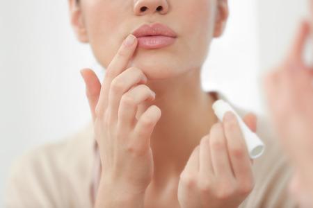 Mujer aplicando bálsamo labial higiénico cerca del espejo