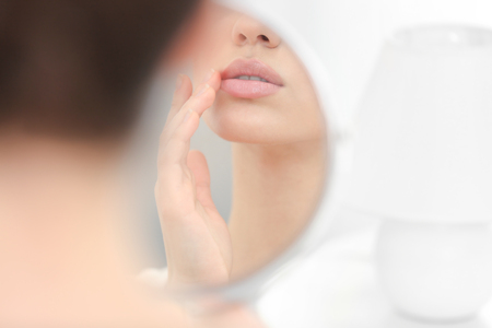 Young woman with cold sore looking in mirror at home Фото со стока
