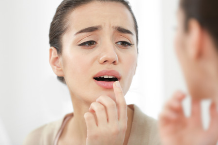 Beautiful woman applying cream onto lips near mirror Zdjęcie Seryjne